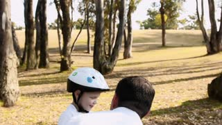 Steadicam shot of father teaching son how to use his his safety helmet on a park pathway.
