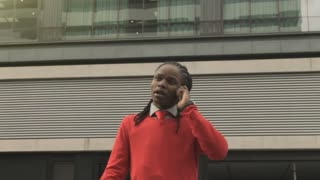 Steadicam shot of good looking African American man doing business on his cell phone in modern city.