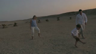 Steadicam shot of happy and active family of three playing with ball on the beach at sunset. Fun and leisure on summer vacation