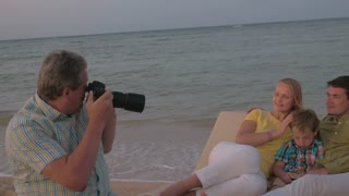 Steadicam shot of mature fotographer taking photos of a family resting on a beach.