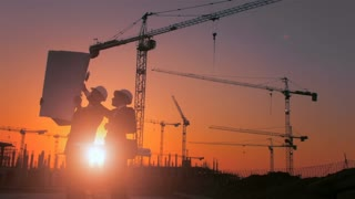 Steadicam shot of skyline and cranes with construction workers