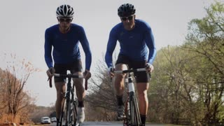 Steadicam shot of two healthy men cycling on road bicycle with speed and sprinting.