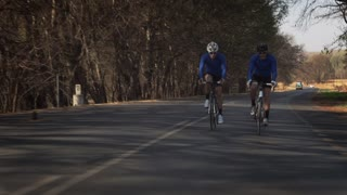 Steadicam shot of two healthy men cycling up the road on a road bicycle.