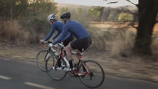 Steadicam shot of two healthy men, drinking water and peddling on road cycling bicycle at sunset.