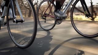 Steadicam shot of two healthy men peddling fast with cycling road bicycle at sunset. With cyclist support vehicle in pursuit.