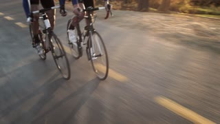 Steadicam shot of two healthy men peddling/ free wheeling with cycling road bicycle at sunset.