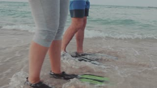 Steadicam shot of two human feet wearing flippers. They are marching by the sea in the incoming waves.