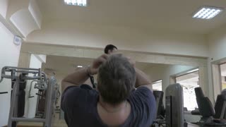 Steadicam shot of two people working out in the gym. One man doing situps on abdominal bench while another one starting chest press after break