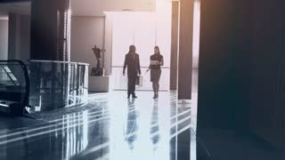 Steadicam shot of young confidant and diverse business team walking with tablet computer in modern glass business building at sunrise.