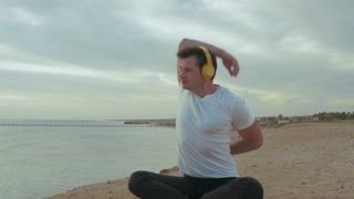 Steadicam shot of young couple having workout on the beach by the sea. They doing exercises while listening to music in wireless headphones and then having a rest looking at sea