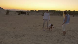 Steadicam shot of young family kicking a little ball on a beach at twilight.