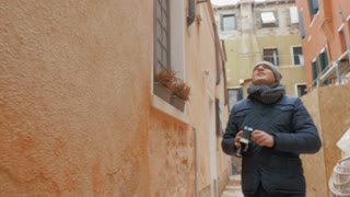 Steadicam shot of young man with vintage handheld camera capturing on video buildings of old city.