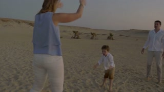 Steadicam shot of young parents and little son playing football on the beach at sunset. Outdoor activity with child