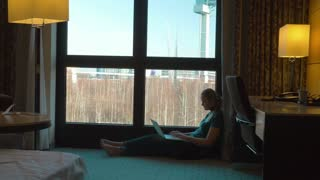 Steadicam shot of young woman using laptop in hotel. She sitting on the floor by the window in cosy room, chatting on computer and enjoying city view
