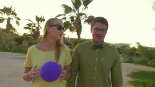 Steadicam shot of young woman walking with hipster style man on tropical resort at sunset. Happy girl playing with violet balloon while having a vivid talk with a friend