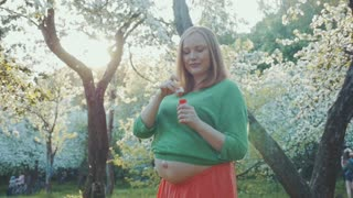 Steadicam slow motion shot of a pregnant woman went for a walk to the park in spring. She's standing surrounded by blooming threes and blowing soap bubbles.