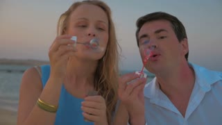 Steadicam slow motion shot of male and female friends blowing soap bubbles. There is sea on the background.