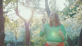 Steadicam slow motion shot of mother-to-be blowing soap bubbles in the park. Sun is shining through the trees.