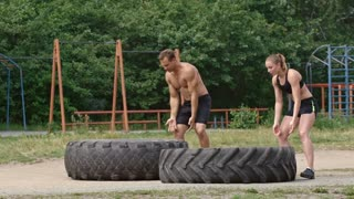 Strong shirtless man pushing heavy tire vertical while sporty young woman trying to do the same in slow motion