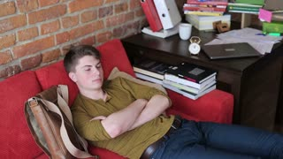 Student having nap on red sofa