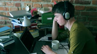 Student listening music with headphones and drinking coffee