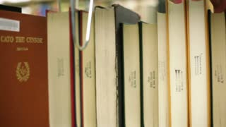 Student Picks Up Book From Shelf
