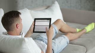 Student relaxing on sofa with tablet