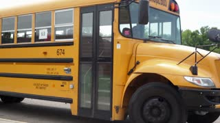 Students File Out of Bus At School