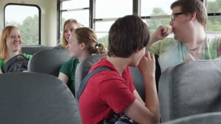 Students Having Fun Talking on Bus