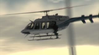 Stuntmen Hangs Onto Side Helicopter