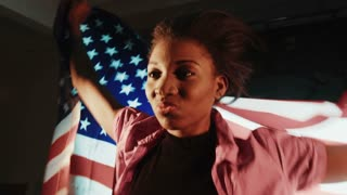 Stylish African American female with American flag in hands on the back looking straight in the camera and shake flag. Patriotic concept or sport fans concept. Movement shot