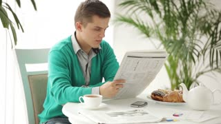 Stylish young man sitting at table reading newspaper looking at camera and turning back to reading
