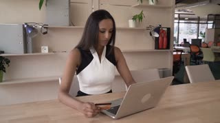 Successful business woman buying via internet. Mixed race young female sitting in the office enter security code on the computer. Customer shopping in e-commerce shop typing number from creditcard