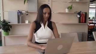Successful indian businesswoman close down laptop after hard project in the modern office. Beautiful mixed race worker finish her typing and turn off computer. Business female sitting at the working