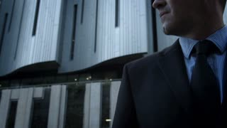 Suits business man fixing his tie before a deal in the city. Steadicam shot.