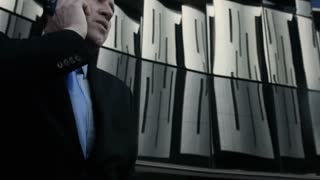 Suits business man talking on his mobile phone in modern glass city. Steadicam shot