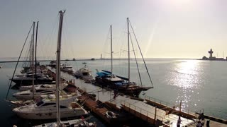 Summer. Morning. Sunny weather. Yachts are the small pier. People walk on the pier. Timelapse