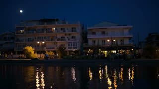 Summer resort by the sea at night with outdoor cafe, hotel and people enjoying their rest. Electric lights reflecting in water