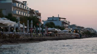 Summer resort in the evening. Hotels and cafes with calm sea in foreground. Recreation and summer vacation