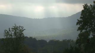 Sun Beams Through Hazy Hillside Sky