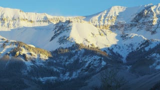 Sun Hits Top of Colorado's Snow-Covered Mountains