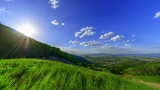 Sun Peeking Over Vibrant Green Hills