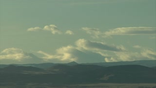 Sun Setting and Clouds Moving Over Mountain Range
