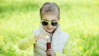 Sunny girl in sunshine blowing soap bubbles outdoors
