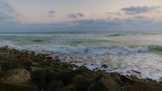 Sunset at Sea. Waves and foam on rocky beach Indian Ocean.