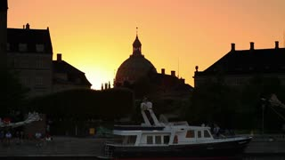 Sunset Silhouette of Church Exterior and Boat Harbor