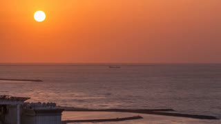 Sunset with reflection in water of Gulf in Ajman citiscape from rooftop timelapse. Ajman is the capital of the emirate of Ajman in the United Arab Emirates. 4K