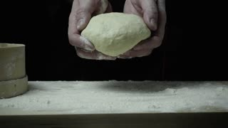 Super slow motion chef tosses dough on a cutting board