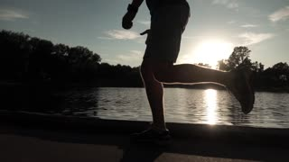 Super slow motion steadicam clip of sunset park runner on pond bank. Bleached