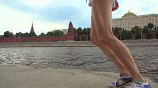 Super slow motion steadicam shot of athletic brunette girl runner against Moscow Kremlin 240 fps